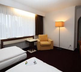 Fotel, stolik kawowy, lozka hotelowe